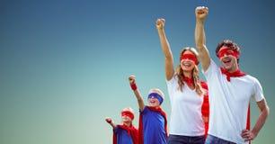 Familjen i superhero kostymerar anseende med lyftta armar arkivfoto