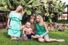 Familjen inkluderar farmodern, modern, flickan och pojken i parkera arkivfoto