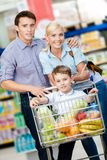 Familjen kör vagnen med mat och pojken som där sitter royaltyfri bild