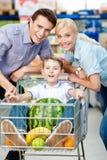 Familjen kör vagnen med mat och pojken som sitter där royaltyfri foto