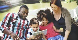 Familjen kopplar av lycka genom att använda minnestavlabegrepp arkivfoton