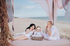 Familjen kopplar av på stranden arkivbilder