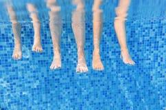 Familjen lägger benen på ryggen undervattens- i simbassängen, bad med barn under det roliga begreppet för vatten, semester med un royaltyfria foton