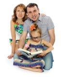 Familjen läser boken Royaltyfri Foto