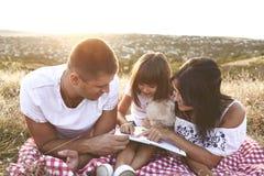 Familjen läser en bok i natur royaltyfri fotografi