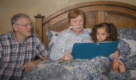 Familjen läser med kvinnan på syre royaltyfria bilder