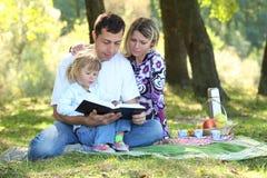 Familjen läste bibeln i natur Arkivbild