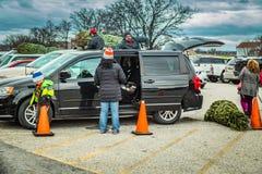 Familjen laddar den nya evergreen till bilen arkivfoto