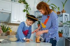 Familjen lagar mat tillsammans Make, fru och deras barn i köket Familjen knådar deg med mjöl royaltyfria bilder