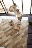 Familjen lurar skrivande in bärande askar för det nya hemmet på rörande dag royaltyfri fotografi