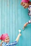 Familjen målar en trävägg av blåttmålarfärg arkivbild