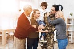 Familjen möter en man i kamouflage hemma royaltyfri foto
