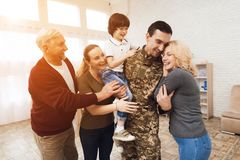 Familjen möter en man i kamouflage hemma royaltyfria foton