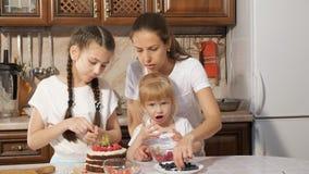 Familjen mamma med två lilla döttrar dekorerar födelsedagkakan med bär tillsammans i kök hemma arkivfilmer