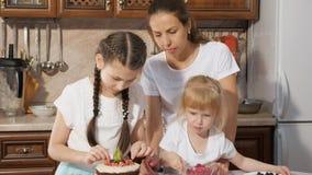 Familjen mamma med två lilla döttrar dekorerar födelsedagkakan med bär tillsammans i kök hemma lager videofilmer
