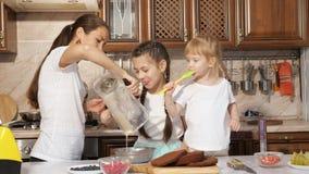 Familjen, mamman och döttrar lagar mat kräm för kaka och häller den i bunke från blandaren stock video