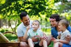 Familjen med barn blåser såpbubblor utomhus royaltyfria foton