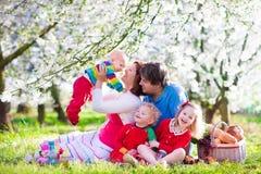 Familjen med barn som tycker om picknicken i vår, parkerar Arkivfoto
