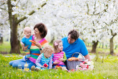 Familjen med barn som tycker om picknicken i vår, parkerar royaltyfria bilder