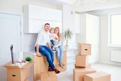 Familjen med barnet flyttar sig till ett nytt hus royaltyfri bild