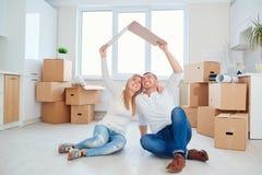 Familjen med barnet flyttar sig till ett nytt hus royaltyfri fotografi