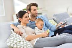 Familjen med behandla som ett barn att tycka om hålla ögonen på tv Arkivfoto