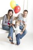 Familjen med ett litet barn är på en gunga Arkivbild