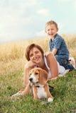 Familjen med hunden har en utomhus- lugna fritid royaltyfri foto