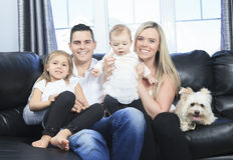 Familjen med husdjur sitter på soffan hemma arkivfoton
