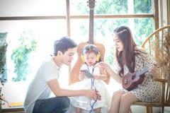 Familjen med lilla flickan lyssnar in till musik på din telefon Royaltyfri Fotografi