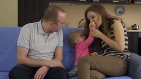 Familjen med lite behandla som ett barn äter det röda nya äpplet sitter på soffan 4K stock video