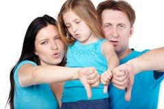 Familjen med oangenäma framsidor ger deras tum Royaltyfri Fotografi