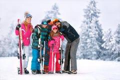Familjen med skidar utrustning som tillsammans ser något Arkivfoton