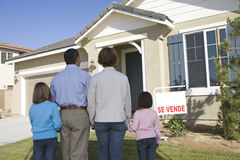 Familjen med två barn (6-8) framme av det nya huset tillbaka beskådar Royaltyfri Foto