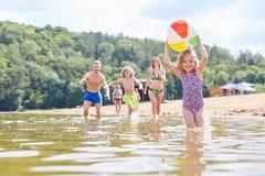 Familjen med två barn spelar med en boll royaltyfria foton