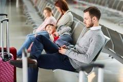 Familjen med två barn väntar i flygplatsen arkivbilder