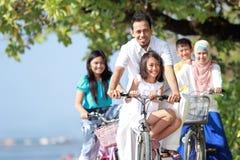 Familjen med ungar tycker om att rida cykeln som är utomhus- i stranden Royaltyfri Foto