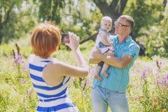 Familjen modern, fader och behandla som ett barn i naturen som fotograferas på phen Royaltyfri Fotografi