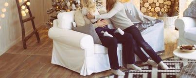 Familjen nära spisen och julgranen sitter på soffan, flickan når ut till hennes fader, kramar honom Congratulatio arkivbilder