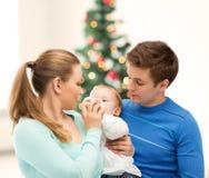 Familjen och förtjusande behandla som ett barn med mata-flaskan Arkivbild