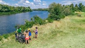 Familjen på cyklar som utomhus cyklar, aktiv uppfostrar och ungar på cyklar, flyg- sikt av den lyckliga familjen med att koppla a arkivbild