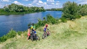 Familjen på cyklar som utomhus cyklar, aktiv uppfostrar och ungar på cyklar, flyg- sikt av den lyckliga familjen med att koppla a arkivfoto