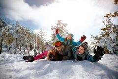 Familjen på vintersemester -, skidar snöar solen och gyckel arkivbild