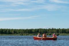 Familjen rider ett träfartyg på sjön i bra väder på semestern, aktiva ferier royaltyfria bilder