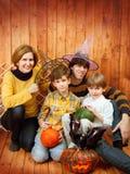 Familjen sitter med allhelgonaaftonens sned pumpa Royaltyfri Fotografi
