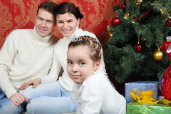 Familjen sitter med gåvor nära julgranen hemma Arkivbild
