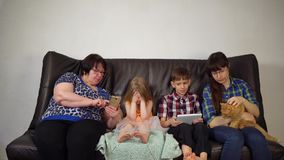 Familjen sitter på soffan och använder digitala grejer lager videofilmer