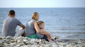 Familjen sitter på stranden lager videofilmer
