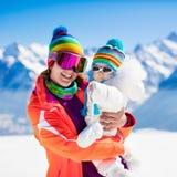 Familjen skidar och snöar gyckel i vinterberg arkivfoto