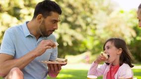 Familjen som äter smörgåsar på picknick på sommar, parkerar stock video
